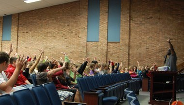 Students all holding hands up in a classroom