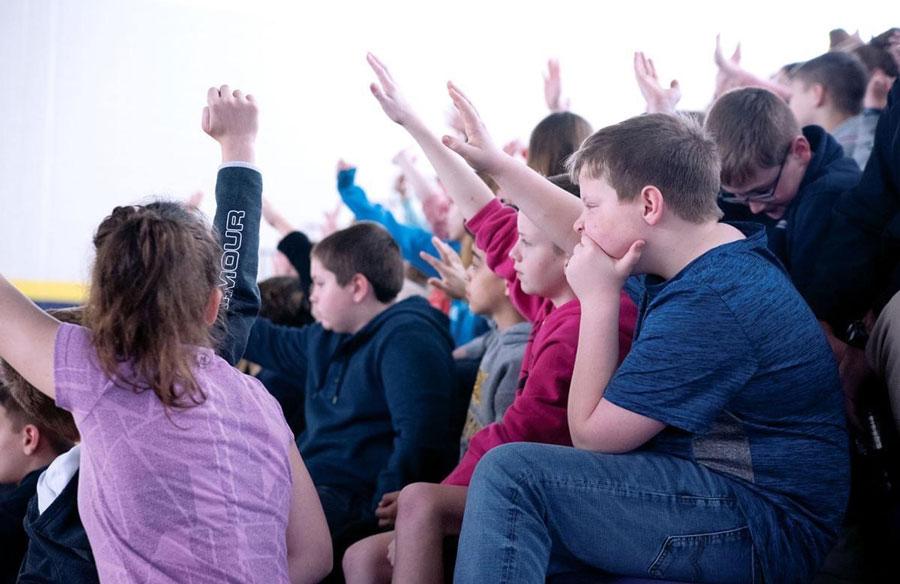 Children all raising their hands, one child with hand under chin