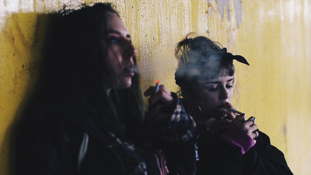 Two women smoking sitting up against wall